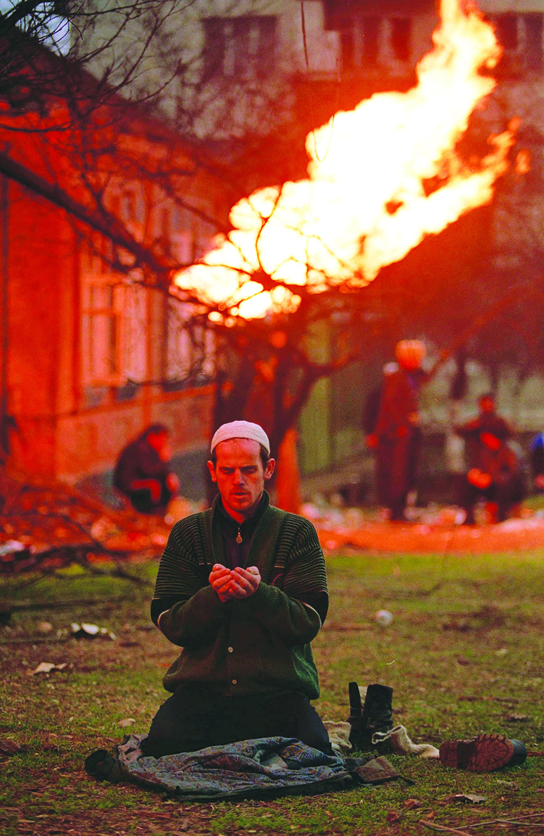 A Chechen man praying during the battle of Grozny in 1995, photo: Mikhail Evstafiev
